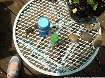Squirrel-gnawed bubble stuff containers on an outdoor table that matches my new shoes.