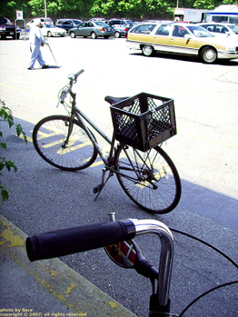 Someone else's bicycle with old milk crate fastened behind seat.
