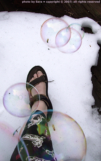 Blowing bubbles on the balcony, one sandaled foot in the snow.