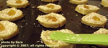 Brushing egg white over cookies.
