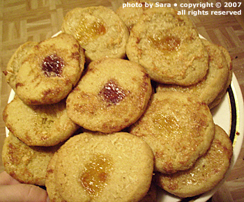 Plate full of baked cookies displaying use of multiple types of jam.