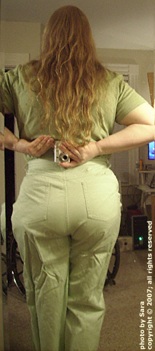 Back of tight women's pants worn over transfemoral prosthetic held on with suction socket and suspension belt.