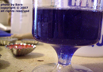 Plastic wine goblet half-filled with ultramarine glitter-sparked resin.