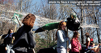 Dragonfly puppet held aloft by red-headed girl.