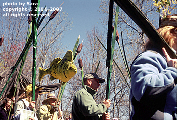 River ecosystem represented by tall parading puppets.