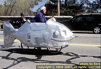 Man wearing a happy metal fish while riding a bicycle.