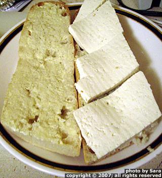 Tofu layered onto sub-in-process.