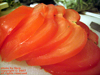 Sliced tomato, glorious and red, but not a roma.
