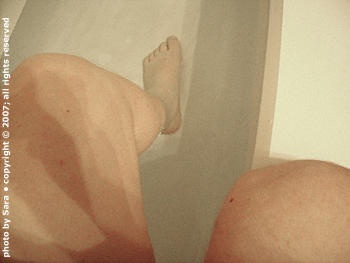 Balancing on side of tub with foot in water.