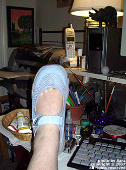 Left foot in new shoe propped up on desk.