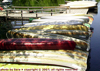 Canoes stacked up at the South Bridge Boathouse, waiting for the season of adventure to begin.