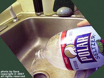 Cranberry-lime-flavored Polar brand seltzer water being poured unceremoniously down the drain.
