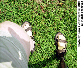 Downhill sideways on grass, prosthetic foot forward.