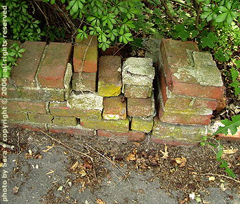 Beautifully imperfect brick retaining wall, gently crumbling.