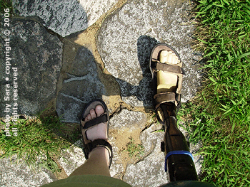Feet walking up a steppingstone path